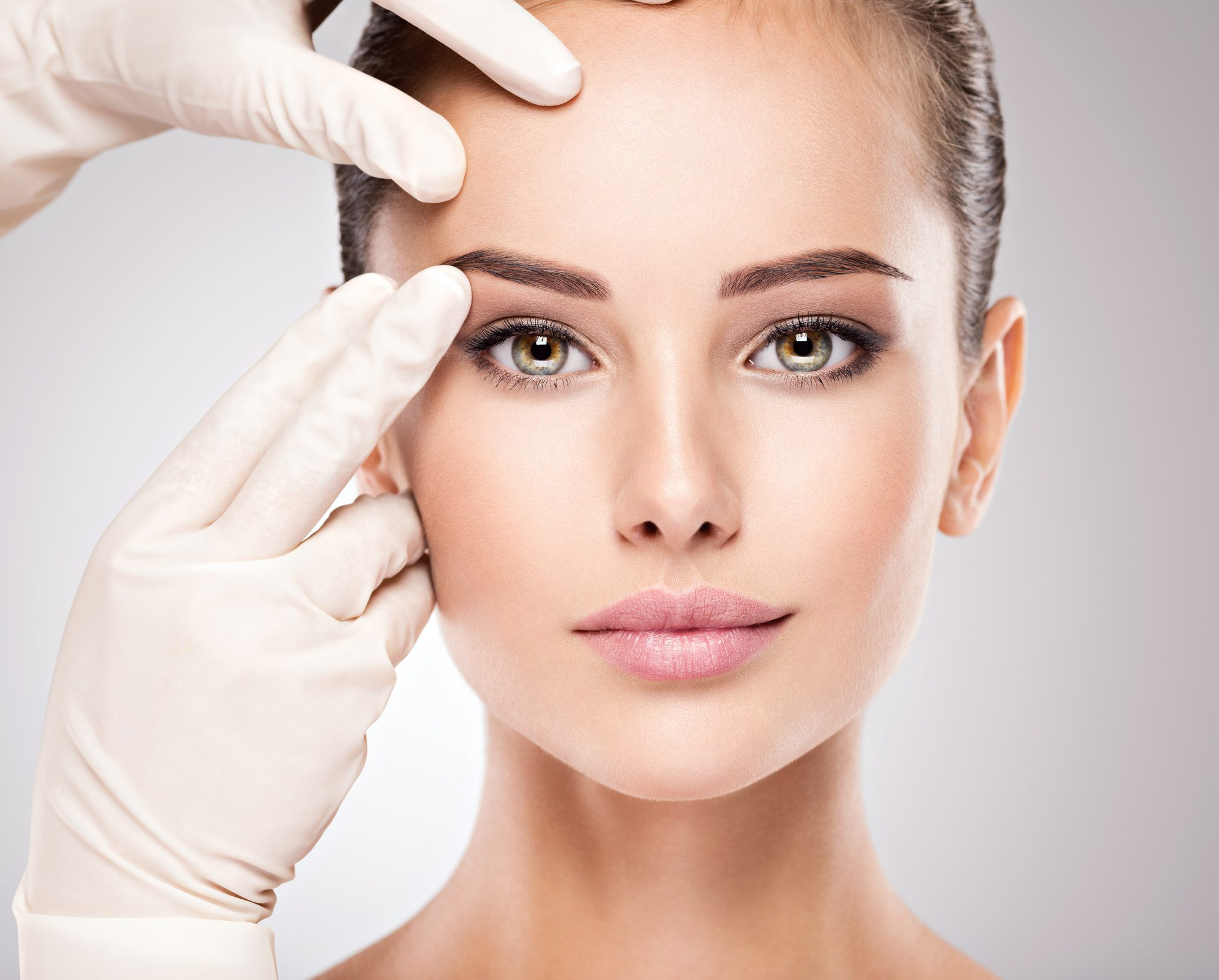 Face skin check before plastic surgery. Beautician touching woman face.